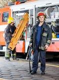 Trasporto del collega di Holding Hose While del pompiere fotografia stock libera da diritti