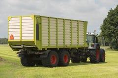Trasporto di erba tagliata con il vagone del caricatore e del trattore Fotografie Stock Libere da Diritti