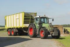Trasporto di erba tagliata con il vagone del caricatore e del trattore Fotografia Stock Libera da Diritti