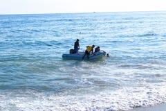 Trasporto di un gruppo di persone su un gommone gonfiabile bianco con un motore Fotografia Stock