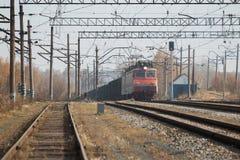 Trasporto locomotivo del treno merci con il carico su luce del giorno Fotografie Stock Libere da Diritti
