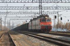Trasporto locomotivo del treno merci con il carico su luce del giorno Immagine Stock Libera da Diritti