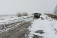 Trasporto privato su una lotta nevosa della strada principale in avanti attraverso il cumulo di neve Immagini Stock
