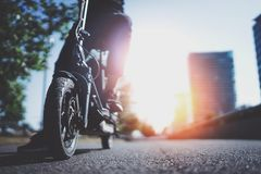 Trasporto urbano elettrico Giovane pronto a guidare la sua bici elettrica del motorino nel centro di una città innovatore fotografie stock