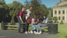 Trastorno al estudiante de los rasgones que se sienta en banco en parque almacen de metraje de vídeo