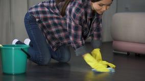 Trastorno de la mujer con el piso y las manchas mal pulidos en el entarimado de madera, limpiando metrajes