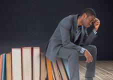 Trastorno del hombre joven que se sienta en los libros apilados por la pizarra Imagen de archivo libre de regalías