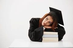 Trastorno y cansado de estudiar la muchacha africana del estudiante y al graduado del futuro que ponen en los libros que piensan  Foto de archivo