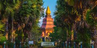 Trat, Thailand: Buddhist temple. A stupa of Wat Phai Lom a Buddhist temple in Trat town, Thailand gilded by the sunset. The palm tree alley leads to it Royalty Free Stock Photos