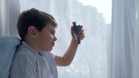 Trata la inflamación de vías aéreas, tubo del inhalador en la boca del niño enfermo que se sienta en el alféizar del hospital almacen de metraje de vídeo