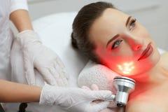 Tratamento claro conduzido vermelho Mulher que faz a terapia facial da pele fotografia de stock