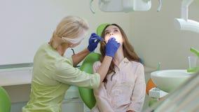 Tratamento da cárie dental no escritório dental Mulher com a boca aberta na cadeira do dentista video estoque