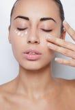 Tratamento de creme cosmético de aplicação modelo bonito em seu branco da cara Foto de Stock Royalty Free