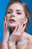 Tratamento de creme cosmético de aplicação modelo bonito em sua cara no azul Foto de Stock