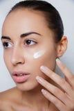 Tratamento de creme cosmético de aplicação modelo bonito em seu branco da cara Imagem de Stock Royalty Free