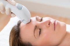 Tratamento de Giving Laser Epilation do esteticista à cara da mulher imagem de stock royalty free