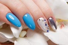 Tratamento de mãos azul do verão bonito na mão fêmea com flores Close-up Fotos de Stock Royalty Free