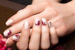 Tratamento de mãos bonito com as flores nos dedos fêmeas Projeto dos pregos Close-up imagem de stock