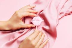 Tratamento de mãos bonito da mulher no fundo cor-de-rosa criativo com tela de seda Tendência minimalista foto de stock