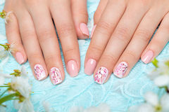 Tratamento de mãos da mola para a noiva em tons delicados com flores Projeto do prego Close-up Foto de Stock