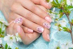 Tratamento de mãos da mola para a noiva em tons delicados com flores Projeto do prego Close-up Fotos de Stock