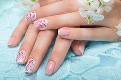 Tratamento de mãos da mola para a noiva em tons delicados com flores Projeto do prego Close-up Imagens de Stock Royalty Free