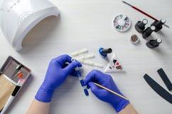 Tratamento de mãos Desktop Vários elementos para o projeto do prego O mestre prepara amostras do projeto flatlay fotos de stock royalty free