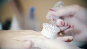 Tratamento de mãos do hardware em uma clínica da cosmetologia Mãos de limpeza do movimento lento da poeira vídeos de arquivo