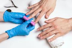 tratamento de mãos do ` s dos homens O Cosmetologist nas luvas de borracha arquiva pregos nas mãos masculinas imagens de stock