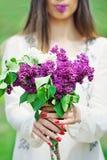 Tratamento de mãos e lilás vermelhos Foto de Stock Royalty Free