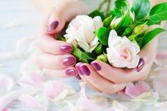 Tratamento de mãos e rosas cor-de-rosa imagem de stock