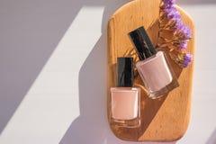 Tratamento de mãos - foto do tratamento da beleza Grupo de cores pastel na placa de madeira Copie o espaço garrafas e flor do ver imagens de stock