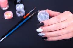Tratamento de mãos preto, branco da arte do prego Tratamento de mãos brilhante do estilo do feriado com sparkles Frasco do lustra Imagens de Stock