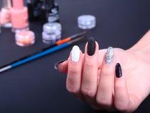 Tratamento de mãos preto, branco da arte do prego Tratamento de mãos brilhante do estilo do feriado com sparkles Frasco do lustra Imagens de Stock Royalty Free