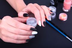 Tratamento de mãos preto, branco da arte do prego Tratamento de mãos brilhante do estilo do feriado com sparkles Frasco do lustra Imagem de Stock Royalty Free