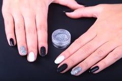 Tratamento de mãos preto, branco da arte do prego Tratamento de mãos brilhante do estilo do feriado com sparkles Frasco do lustra Fotografia de Stock Royalty Free