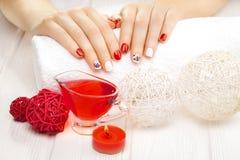 Tratamento de mãos vermelho com dekor Termas Imagem de Stock