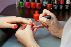 Tratamento de mãos, vermelho do verniz de prego Fotos de Stock