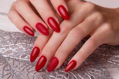 Tratamento de mãos vermelho festivo brilhante nas mãos fêmeas Projeto dos pregos fotografia de stock