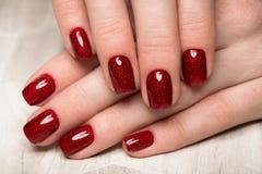 Tratamento de mãos vermelho festivo brilhante nas mãos fêmeas Projeto dos pregos imagens de stock royalty free