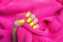 Tratamento de m?os f?mea na moda ? moda Pregos amarelos de néon no fundo cor-de-rosa plástico foto de stock