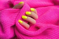 Tratamento de m?os f?mea na moda ? moda Pregos amarelos de n?on no fundo cor-de-rosa pl?stico imagem de stock royalty free