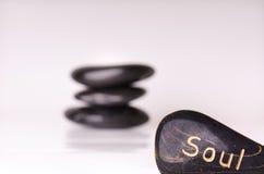 Tratamento de pedra Pedras de massagem pretas em um fundo branco Pedras quentes balanço o zen gosta de conceitos Pedras do basalt Imagem de Stock Royalty Free