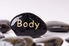 Tratamento de pedra Pedras de massagem pretas em um fundo branco Pedras quentes balanço o zen gosta de conceitos Pedras do basalt Fotografia de Stock