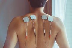 Tratamento dos DEZ na fisioterapia Homem novo com DEZ em seu b imagens de stock