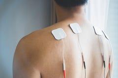 Tratamento dos DEZ na fisioterapia Homem novo com DEZ em seu b foto de stock royalty free