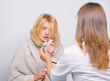 Tratamento e quando chamar o doutor Mulher do doutor para examinar a pessoa doente Reconheça sintomas do frio Doutor de visita da fotografia de stock
