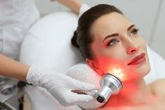 Tratamento facial da beleza Mulher que faz a terapia clara conduzida vermelha imagens de stock