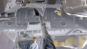 Tratamiento anticorrosivo de la parte inferior del coche por los robots modernos, colores de rociadura almacen de metraje de vídeo