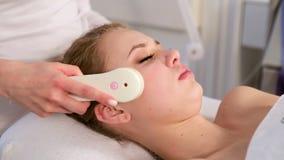 Tratamiento de alta frecuencia de la piel de la cara femenina en balneario almacen de video